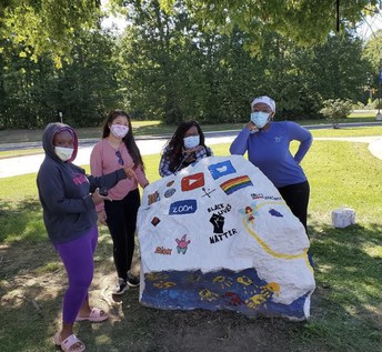 four students wearing masks by painted rock with variety of logos