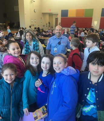 Captain Joe from OJRSD Safety and Security is greeted by a swarm of third grade students with homemade cards