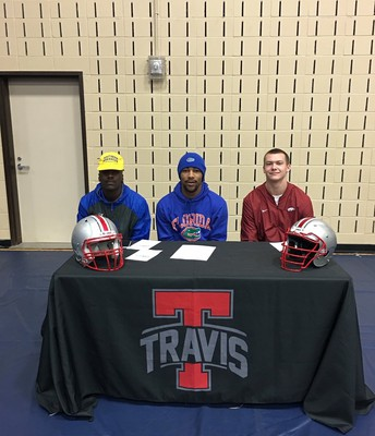 Travis Football Seniors, Nate W., Arjei H., and Zach Z sign their NLI on National Signing Day!