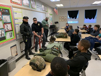 3 police officers talking to students