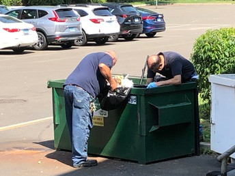 Western Middle School Custodians looking for a lost student item in the dumpster