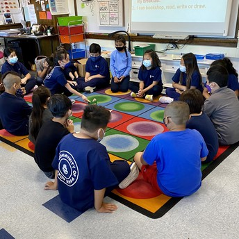 Students sit in a circle