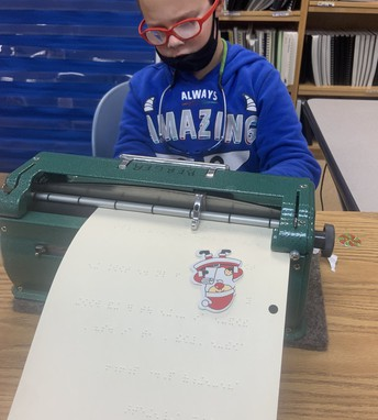 Student sitting at a brailler with brailled paper and a raised Santa sticker