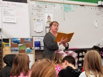 Mrs. Moore is reading one of her favorite books to a class.