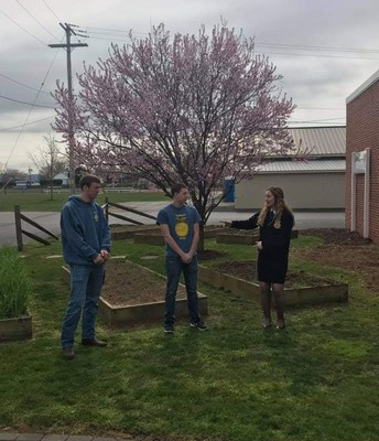 Chapter President Hayden Phillips introduces fellow seniors Sam Witman and Tanner Kline to explain the program's use of the raised garden beds.