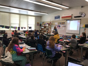 Ms. Klimek working with her 6th graders  on a novel on Friday