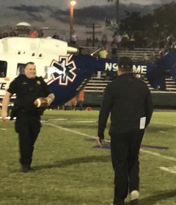 Jeff Ferry, presidente de la junta de LISD, entregando la bola del juego por helicóptero al entrenador Martin