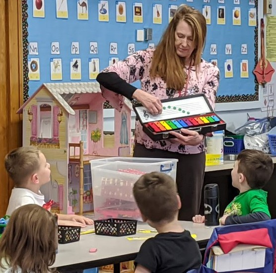 Music teacher Mrs. Sharon Monarchino demonstrating magnetic notes on a musical staff for Park Elementary Kindergarten students in Mrs. Setzer's class.