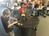 Sharing out with classmates and creating with play dough.
