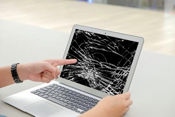 Picture of a laptop with a broken screen and someone pointing to it.