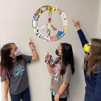 Three students point to their contribution to a Peace Puzzle on the wall of the classroom.