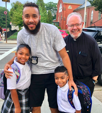 Officer Lopes and Father Jack welcome Maliyah and Milan back to school!