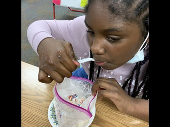 Student eating ice cream with sprinkles out of a plastic ziploc bag