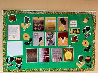 bulletin board; green paper background with sunflower border; poster set of Amanda Gorman and her poetry, with predominant colors of brown and yellow; print and brailled biographical information included