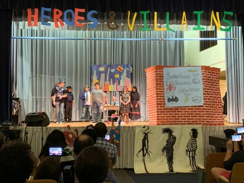 OSSB students are shown on stage in the middle of a skit during the Spring concert.  A sign hangs over the stage that says Heroes & Villains. On stage, a brick wall is shown with a sign that says Superhero Training Academy. Shown in the foreground of the photo are various audience members taking photographs of the young actors and actresses.