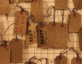 Photo of paper tags with prayers written on them hanging from a wire mesh against a wall
