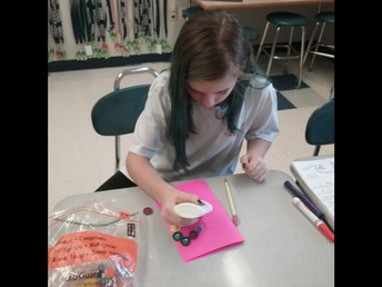 A new member of the Kindness Club makes a farewell card for a kindergarten student whose last day was Friday.