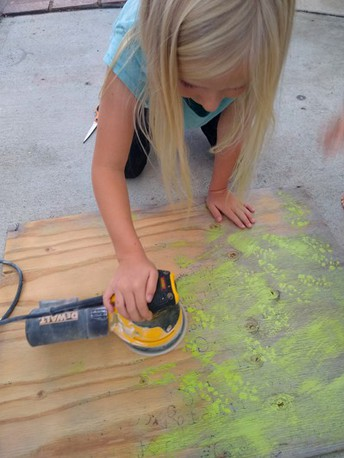 Olive, 1st grade, sanding the old wood sign to prepare for the new design.