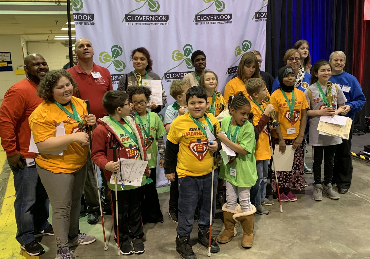 OSSB Students and staff at the Braille Challenge at Clovernook in Cincinnati.  Students shown have medals, certificates, and trophies and many stand holding their white canes.  Left to right in front row are Brian, Lyric, Wesson (partiallly obsured), Jayven, Mikaia, Philip, Amina and Jana. In the back row are Mr. Ransey, Mr. Kelley, Aujanee, Elliott, Perseus, Taylor, Matt (partially obscured), Mrs. FInley, Emily, and Mrs. Peirano. Not shown are Dr. Maynus and Mrs. Kaplan.