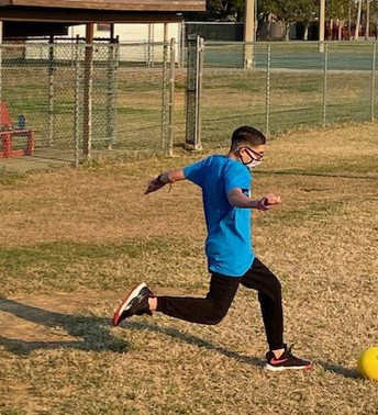 A student shows good form as they run to meet the ball just before kicking it