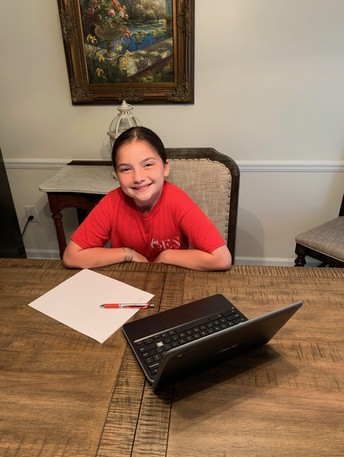 female student smiling at home table with laptop