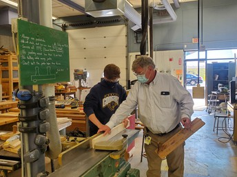 Mr. Morris teaching student on using a planer in woodworking class.
