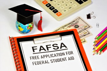 FAFSA spelled out on a clipboard and other items such as a calculator, money bills, small globe with graduation hat.