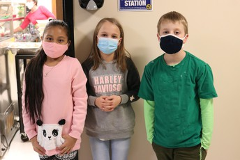 two girls and a boy wear face masks and stand outside the door to the school cafeteria