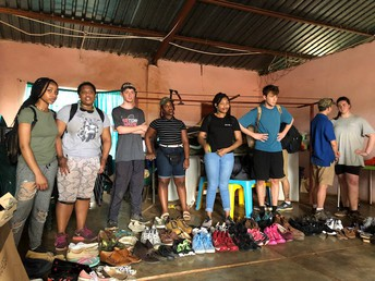 Students from Wamogo and GEMS wait to assist people with finding their perfect pair of shoes.