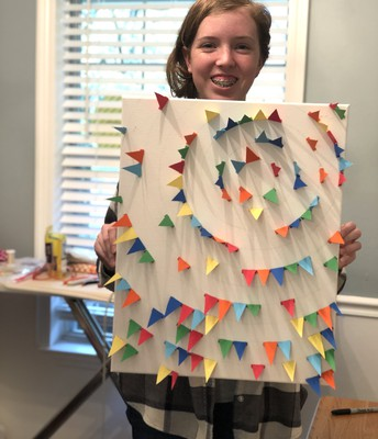 Sadie making art with paper and a canvas!