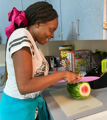 Student is using a large kitchen knife to slice a whole watermelon. She has a big pink bow in her hair and is smiling
