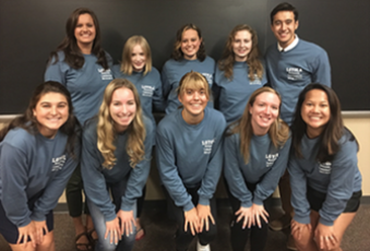 Group of 10 Koinonia leaders wearing blue Koinonia shirts smiling in front of a blackboard
