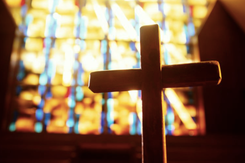 Cross with sun streaming through stained glass in the background