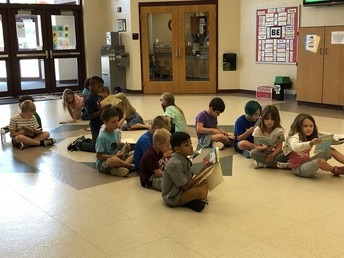 Second grade reading quietly in the hall