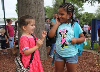 Two young students with backpacks talk and laugh on the first day of school