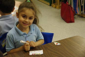 kelly school female student performing subtraction activity with index card and stickers
