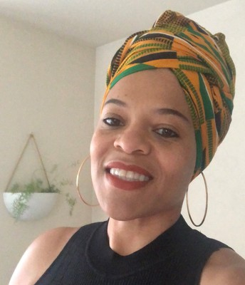 Lorrie wears a green, yellow, and black head wrap and smiles at the camera.  A white planter hangs on a wall behind her. Large gold hoops fashionably hang from her ears.