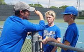 Coach Latham helps a doubles team at the Jr. High tennis tourney