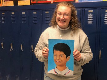 Jaylynn Rentas holds her finished painting of young orphan boy.