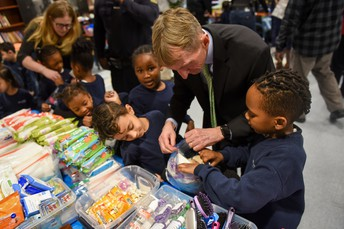 Commissioner Evans fills a Blessing Bag with Stephen and Brandon!