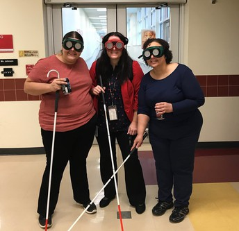 OSSB Staff, Ms. Martin, Dr. LaBarre, and Ms. Harlan trying to pose for a group photo with their vision simulators and canes, and without knowing where the camera is!