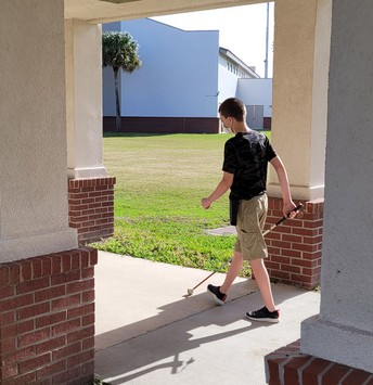 Jasen walking away from the camera. He is between several poles on a sidewalk with the sun shining from the east