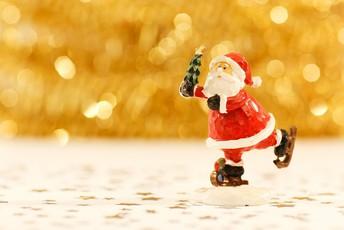 Santa Clause ice skating holding a tree