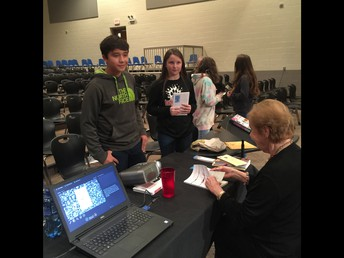 An 8th grader waiting while Mrs. Lazan autographs his book