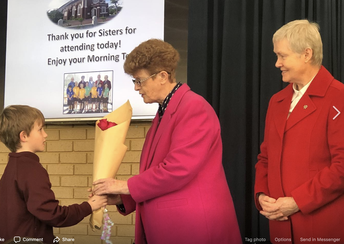 Sr Maureen Moynihan (past Principal) receiving flowers on St Thomas' Feast Day with Sr Irene