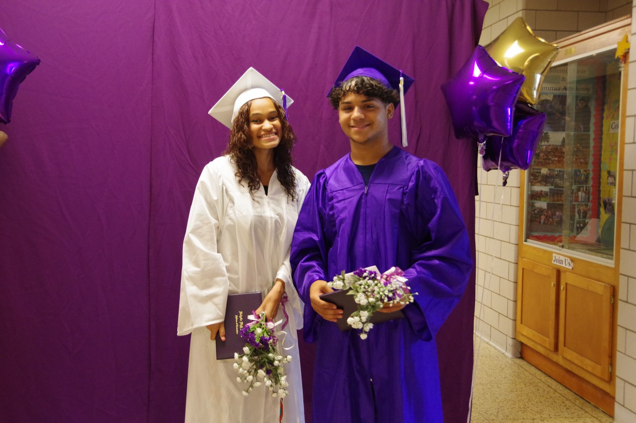 high school graduates in purple and white caps and gowns