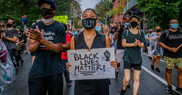 Woman holding a Black Lives Matter sign at a march