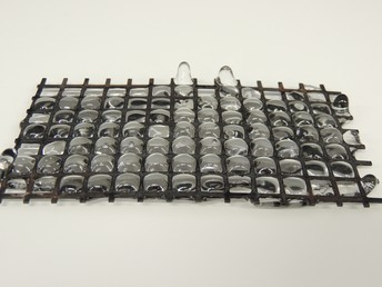 Melting glass through a metal grid by Haylina Reece.