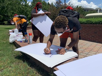 Three students write on posterboards while wearing cloth masks and wearing backpacks. Trees and university buildings are visible in the background.