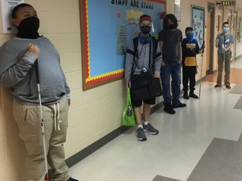 5 middle school students standing against the wall in the school hallway